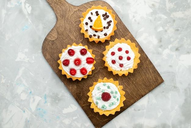 Bovenaanzicht kleine slagroomtaartjes met fruit op het lichtgrijze suikerzoete oppervlak