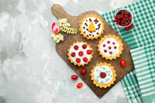 Bovenaanzicht kleine slagroomtaartjes met vers fruit op het lichtgrijze suikergoed