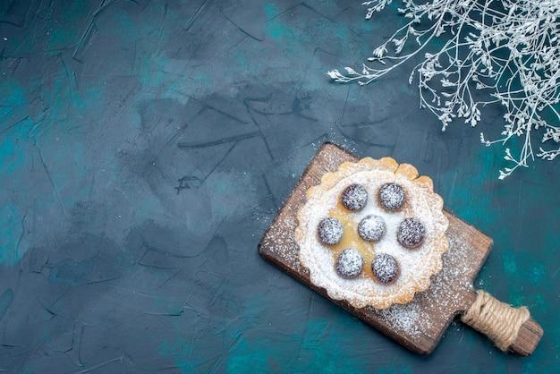 Bovenaanzicht kleine suiker-poeder cake met fruit op de donkerblauwe achtergrond cake biscuit fruit zoete suiker