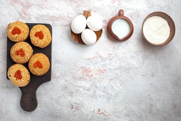 Bovenaanzicht kleine suikerkoekjes heerlijke snoepjes voor thee met eieren en melk op witte desk pie cookie sugar biscuit sweet cake