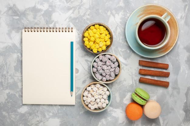 Bovenaanzicht kleine suikersuikergoed met kopje thee en franse macarons op witte achtergrond cake koekje thee zoete suiker
