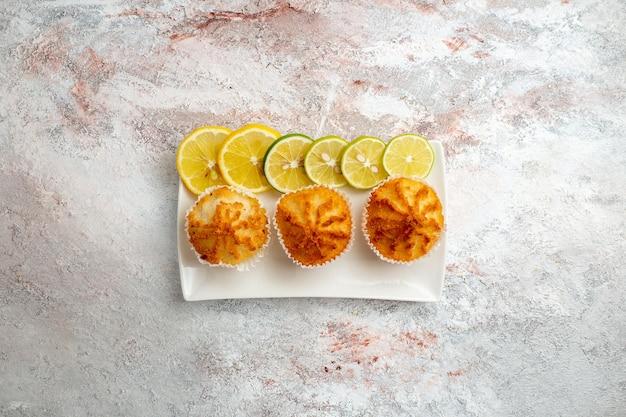 Bovenaanzicht kleine taarten gebakken en met schijfjes citroen op witte ondergrond