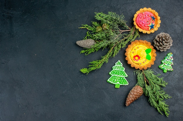 Bovenaanzicht kleine taarten kerstboom cookies dennenappels pine branchees op donkere tafel met kopie ruimte