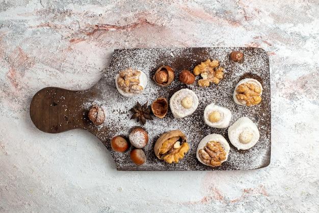 Bovenaanzicht kleine taarten met walnoten en hazelnoten op witte ondergrond
