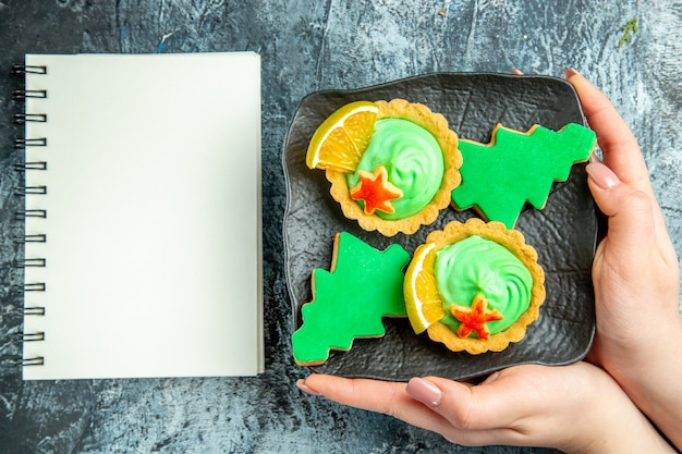 Bovenaanzicht kleine taartjes kerstboom koekjes op zwarte plaat in vrouwelijke hand notebook op grijze tafel