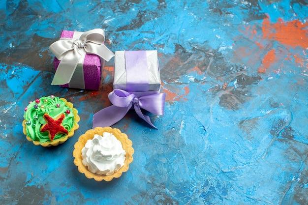 Bovenaanzicht kleine taartjes kleine geschenken op blauwe rode tafel met kopie plaats