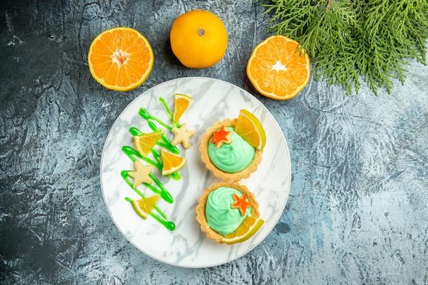 Bovenaanzicht kleine taartjes met groene banketbakkersroom en schijfje citroen op plaat gesneden sinaasappelen kladblok op donkere tafel