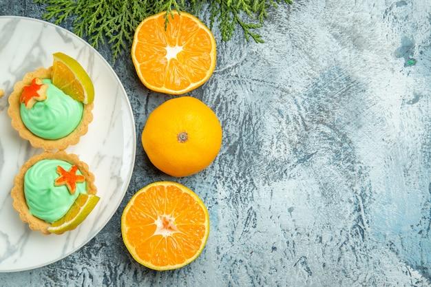 Bovenaanzicht kleine taartjes met groene banketbakkersroom en schijfje citroen op plaat gesneden sinaasappelen op donkere tafel met kopie ruimte