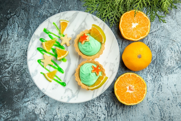 Bovenaanzicht kleine taartjes met groene banketbakkersroom en schijfje citroen op plaat gesneden sinaasappelen op donkere tafel