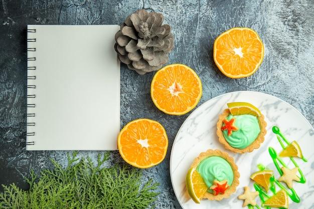Bovenaanzicht kleine taartjes met groene banketbakkersroom en schijfje citroen op plaat gesneden sinaasappels notebook op donkere tafel