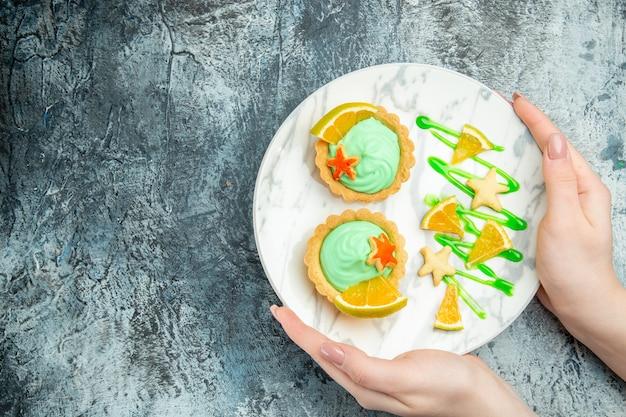 Bovenaanzicht kleine taartjes met groene banketbakkersroom en schijfje citroen op plaat in handen van de vrouw op donkere tafel met vrije plaats