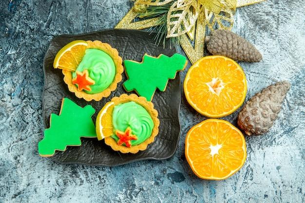 Bovenaanzicht kleine taartjes met groene banketbakkersroom kerstboom koekjes op zwarte plaat xmas ornament gesneden sinaasappelen op grijze tafel