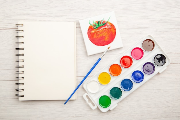 Bovenaanzicht kleine tomaat tekening met kleurrijke verf op witte tafel