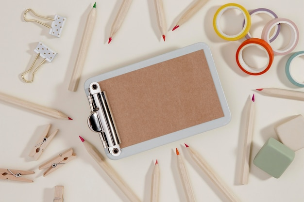 Bovenaanzicht klembord met potloden op tafel
