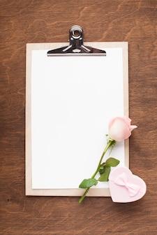 Bovenaanzicht klembord met roze roos en cadeau