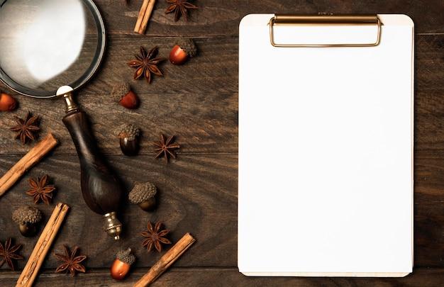 Bovenaanzicht klembord met vergrootglas op tafel