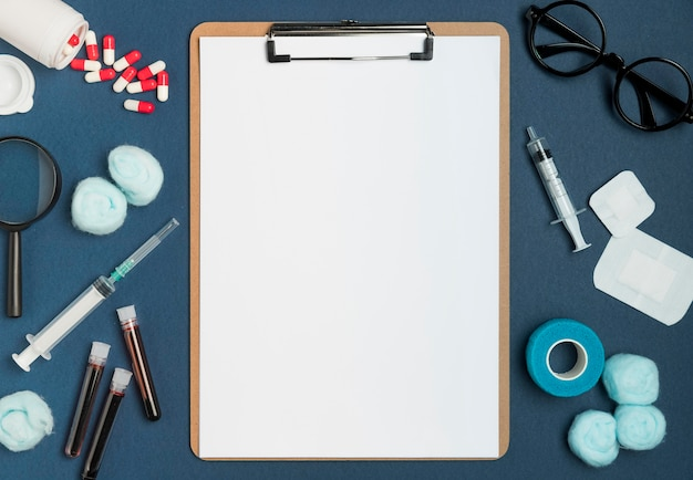 Bovenaanzicht klembord omgeven door medische hulpmiddelen