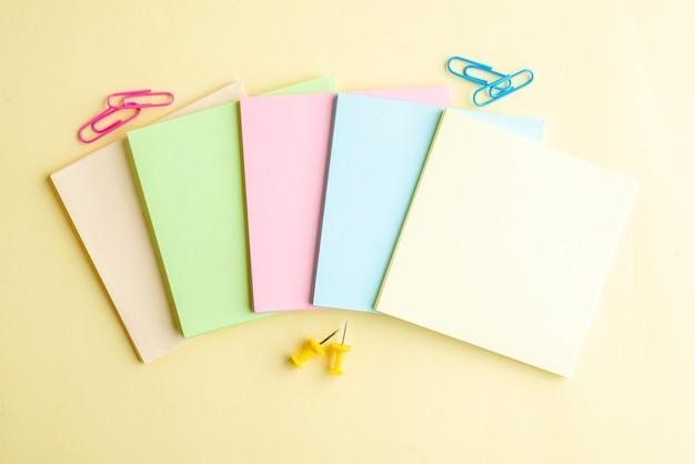 Bovenaanzicht kleurrijke aantekeningen op papier op lichte achtergrond voorbeeldenboek bank bedrijf school kantoor blocnote pen baan geld werk