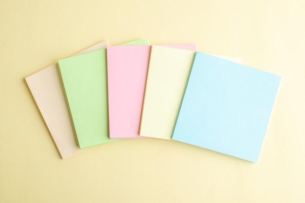 Bovenaanzicht kleurrijke aantekeningen op papier op lichte achtergrond voorbeeldenboek school kantoor blocnote business pen baan geld bank werk