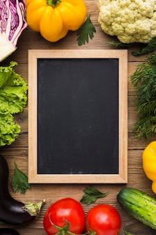 Bovenaanzicht kleurrijke achtergrond met groenten en bord