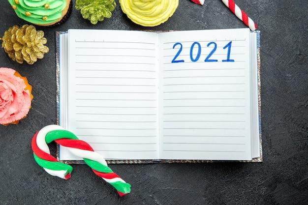Bovenaanzicht kleurrijke cupcakes geschreven op notebook xmas snoepjes en ornamenten op donkere achtergrond