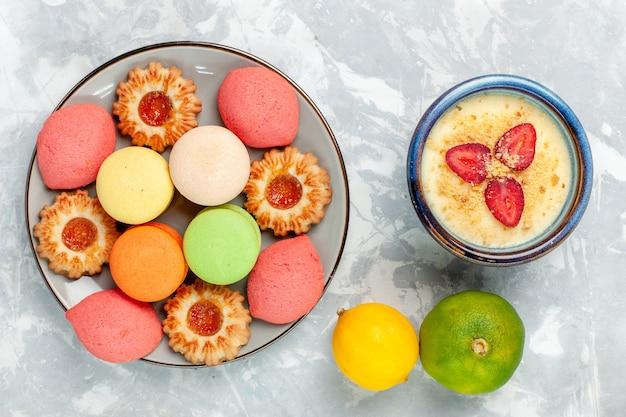 Bovenaanzicht kleurrijke franse macarons heerlijke taarten met koekjes en dessert op witte ondergrond bakken cake zoete suiker dessert koekje