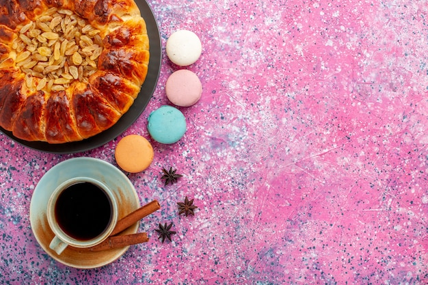 Bovenaanzicht kleurrijke franse macarons heerlijke taarten met thee en kaneel op roze bureau suiker bakken biscuit koekjes cake taart thee