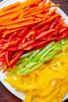 Bovenaanzicht kleurrijke gesneden paprika op witte plaat