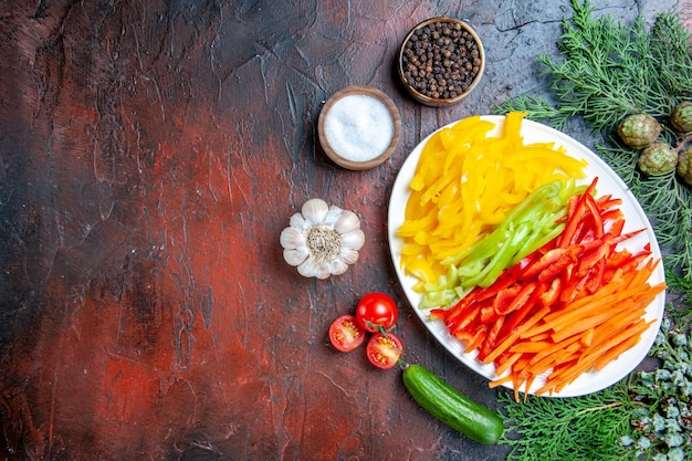 Bovenaanzicht kleurrijke gesneden paprika's op plaat zout en zwarte peper tomaten knoflook komkommer op donkerrode tafel vrije ruimte