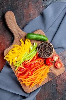 Bovenaanzicht kleurrijke gesneden paprika zwarte peper tomaten komkommer op snijplank op ultramarijn blauwe sjaal op donkerrode tafel