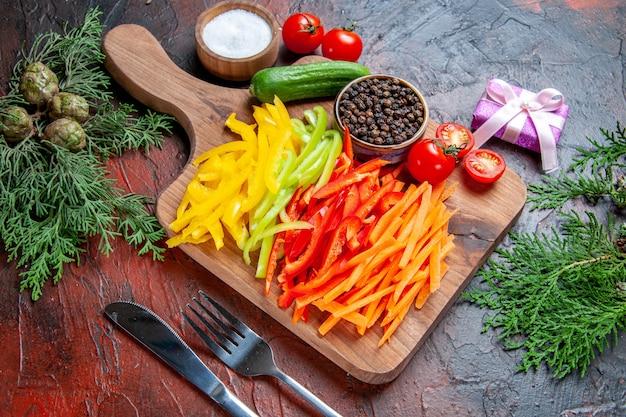 Bovenaanzicht kleurrijke gesneden paprika zwarte peper tomaten komkommer op snijplank zout vork en mes klein cadeautje op donkerrode tafel