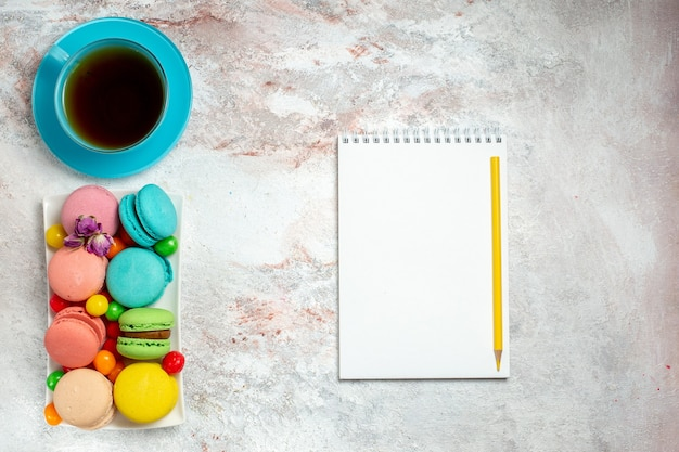 Bovenaanzicht kleurrijke heerlijke macarons kleine cakes met snoepjes op lichte witte ruimte