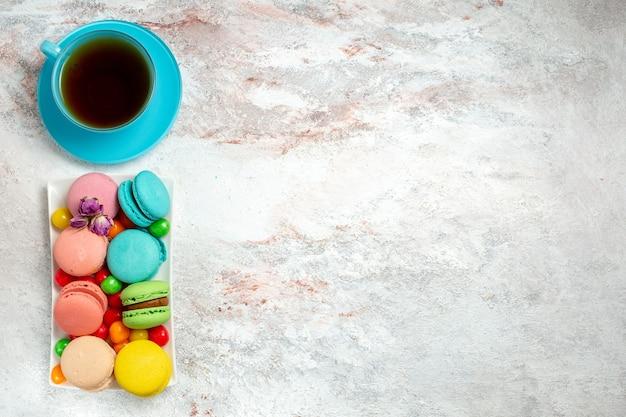 Bovenaanzicht kleurrijke heerlijke macarons kleine cakes met snoepjes op wit bureau