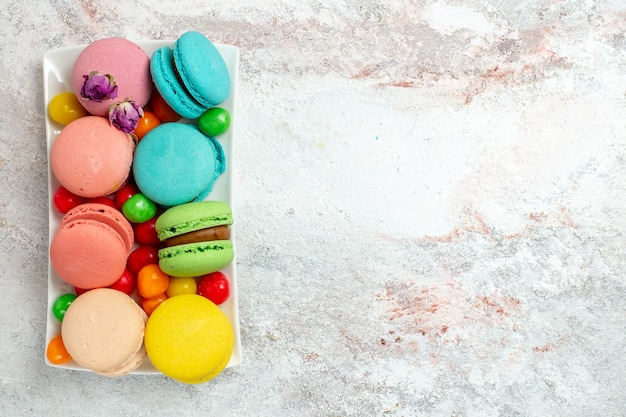 Bovenaanzicht kleurrijke heerlijke macarons kleine cakes met snoepjes op witte ruimte