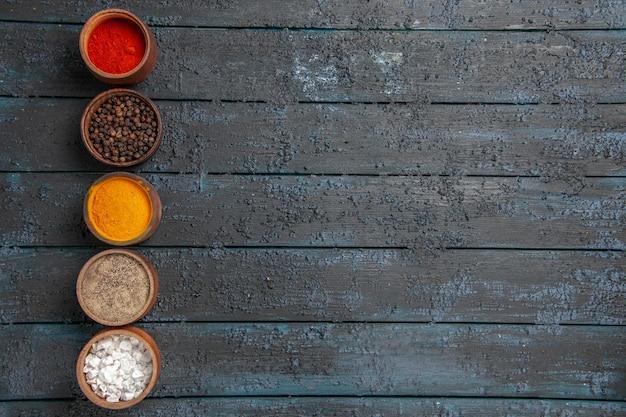 Bovenaanzicht kleurrijke kruiden een rij met verschillende kleurrijke kruiden aan de linkerkant van de tafel