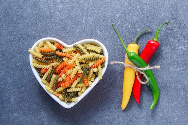 Bovenaanzicht kleurrijke macaroni pasta in hartvormige kom met peper op grijze ondergrond. horizontaal