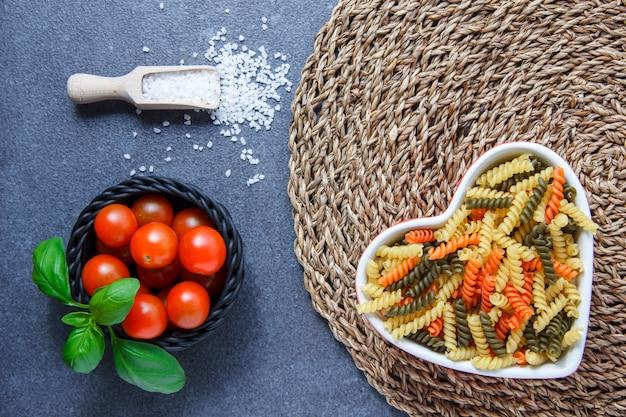 Bovenaanzicht kleurrijke macaroni pasta in hartvormige kom met tomaten, bladeren, kristalzout op onderzetter en grijs oppervlak. horizontaal