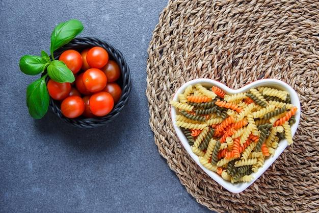 Bovenaanzicht kleurrijke macaroni pasta in hartvormige kom met tomaten in een kom, bladeren op onderzetter en grijze ondergrond. horizontaal