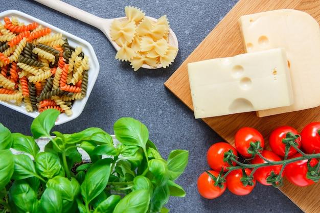 Bovenaanzicht kleurrijke macaroni pasta in kom met tomaten, bladeren, kaas op grijze ondergrond. horizontaal