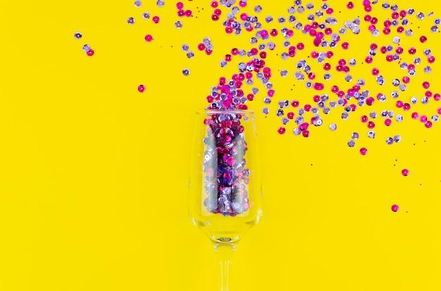 Bovenaanzicht kleurrijke pailletten in een wijnglas