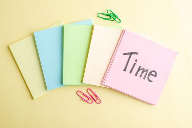 Bovenaanzicht kleurrijke papieren notities met tijd schrijven op een van hen op lichte achtergrond voorbeeldenboek baan bank bedrijf school kantoor blocnote pen geld werk
