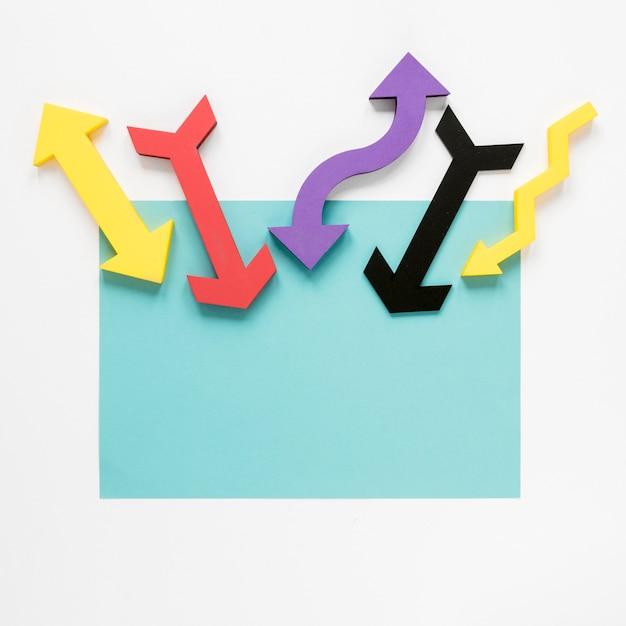 Bovenaanzicht kleurrijke pijlen en blauw karton op witte achtergrond