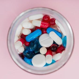 Bovenaanzicht kleurrijke pillen in pot