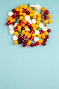 Bovenaanzicht kleurrijke pillen op de blauwe achtergrond