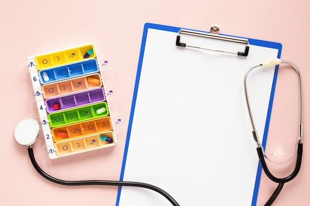 Bovenaanzicht kleurrijke pillendoosje met stethoscoop