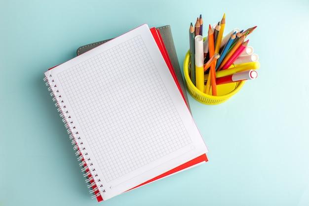 Bovenaanzicht kleurrijke potloden met voorbeeldenboek op de blauwe kleur van de de schoolwetenschap van het muurboek