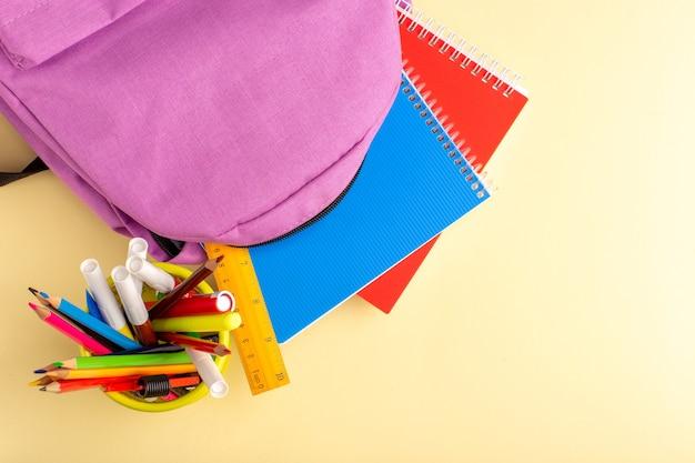 Bovenaanzicht kleurrijke potloden met voorbeeldenboeken en tas op lichtgele muur school viltstift potlood boek kladblok