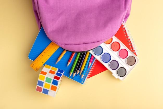 Bovenaanzicht kleurrijke potloden met voorbeeldenboeken verf en paarse tas op lichtgeel bureau school viltstift potlood boek kladblok