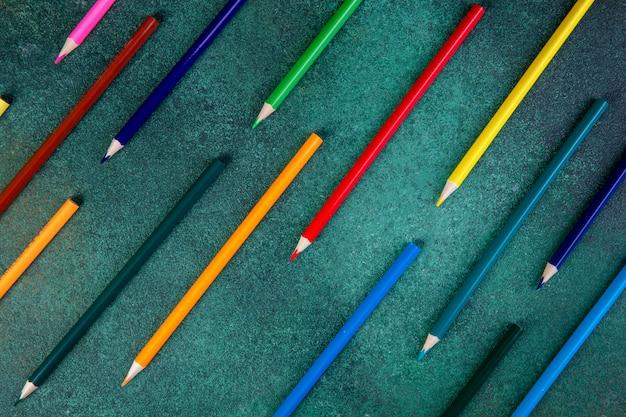 Bovenaanzicht kleurrijke potloden op een groene achtergrond