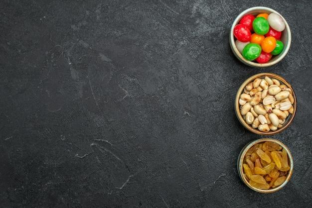 Bovenaanzicht kleurrijke snoepjes met noten en rozijnen op donkere ruimte
